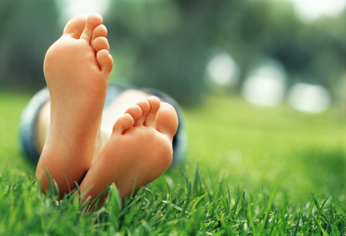 141814772-young-woman-lying-in-grass-with-crossed-feet-gettyimages
