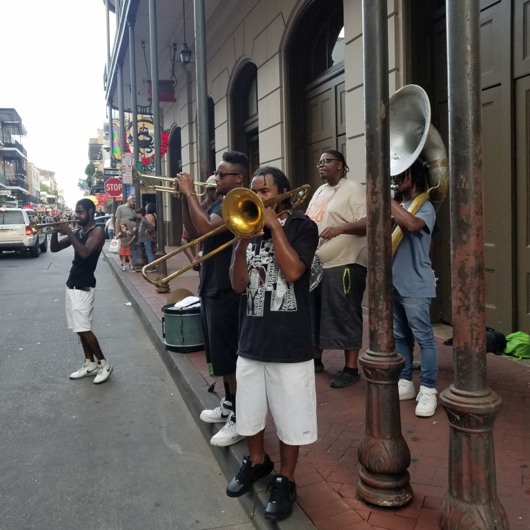 Musical group with tuba, trombone, 2 trumpets and a drum playing on the sidewalk of a small street in the French Quarter