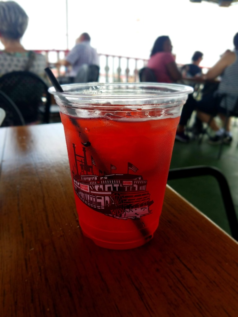 Red cocktail served in a plastic cup