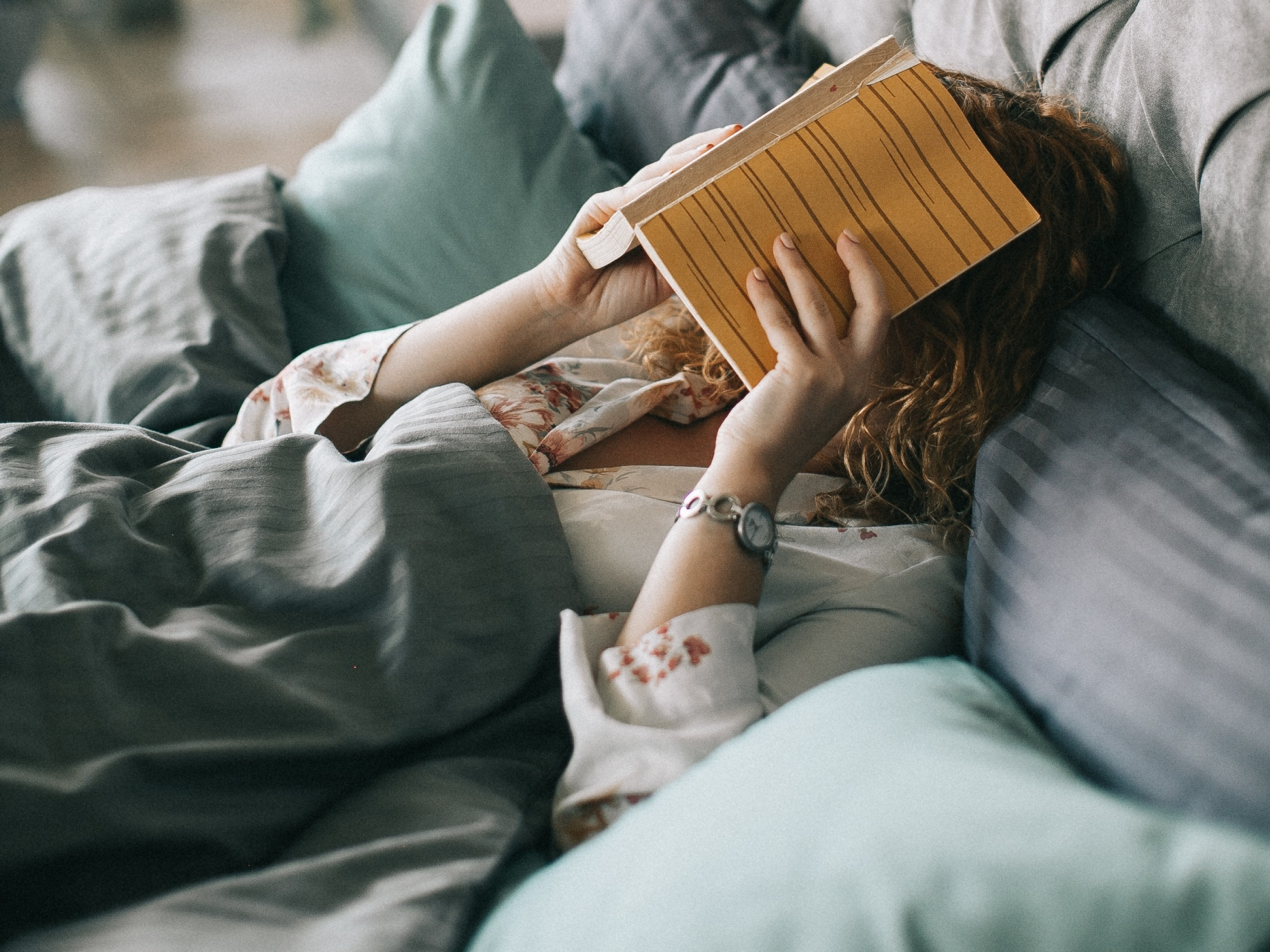 Woman on bed covering her face with a book